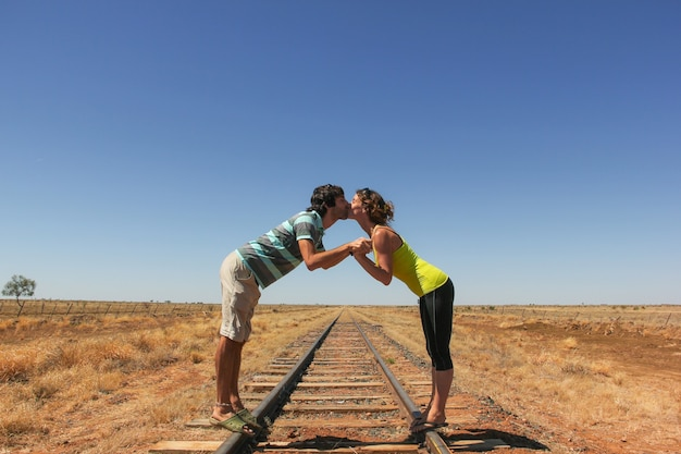 Young couple kissing on railroad in the desert in outback australia. backpacker lovers concept