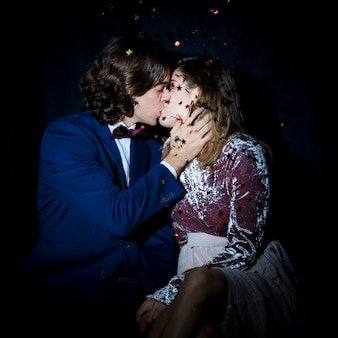 Young couple kissing under spangles
