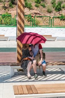 벤치에 앉아있는 동안 우산 아래에서 키스하는 젊은 부부
