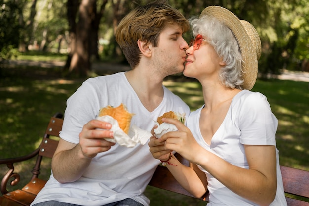 Young couple kissing while enjoying burgers in the park