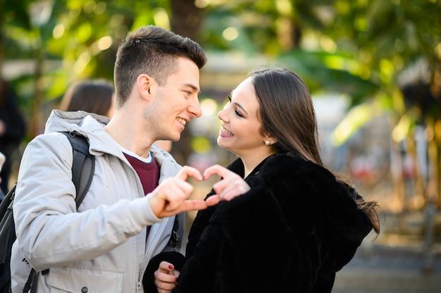 그들의 손으로 하트 모양을 만드는 동안 키스하는 젊은 부부