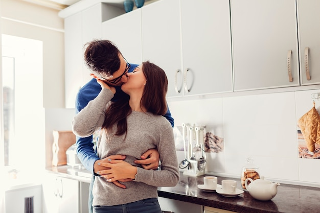 Young couple in the kitchen hugging and kissing
