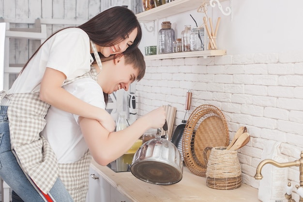 Young couple on the kitchen. man and woman cooking. boyfriend and girlfriend indoors on the kitchen.