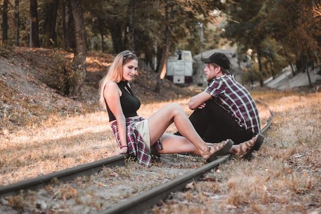 기차에 늦은 젊은 부부 연인은 레일에 기차를 기다리고 있습니다