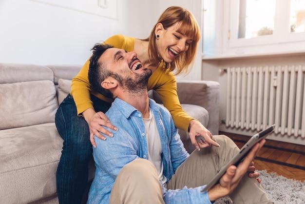 Молодая пара смеется дома в гостиной с помощью цифрового планшета. мужчина и женщина, сидя на диване, улыбаясь с компьютером