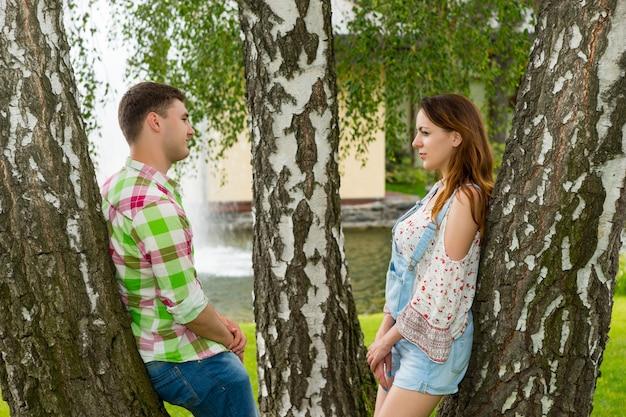 젊은 부부는 나무에 기대어 분수와 다른 나무를 배경으로 공원에서 서로를 바라보고 있습니다.