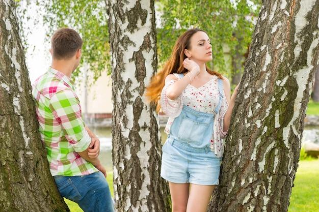 분수와 다른 나무가 있는 공원에서 나무에 기대어 젊은 부부