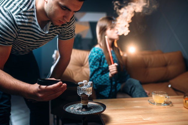 Young couple leisure at night club, smoking hookah, tobacco smoke and relaxation