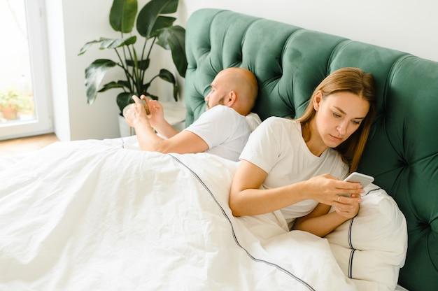 若いカップルが携帯電話でベッドに横になり、お互いに背を向ける