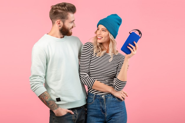 Young couple listening to music on wireless speaker wearing cool stylish outfit smiling posing on pink