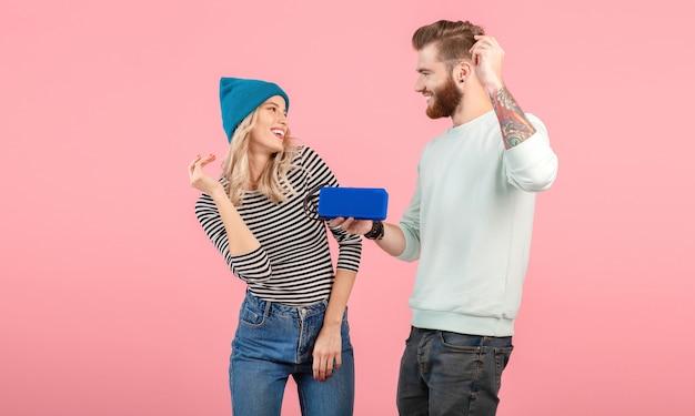 핑크에 포즈 웃 고 멋진 세련 된 옷을 입고 무선 스피커에서 음악을 듣고 젊은 부부
