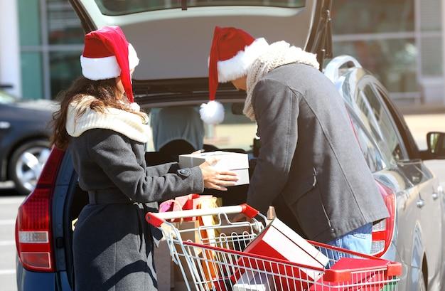 ショッピングモールの駐車場で車のトランクにクリスマスの購入をロードする若いカップル