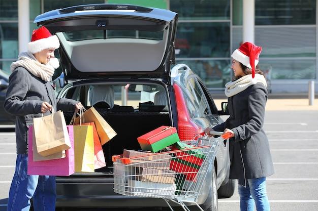 Молодая пара загружает рождественские покупки в багажник автомобиля на парковке торгового центра