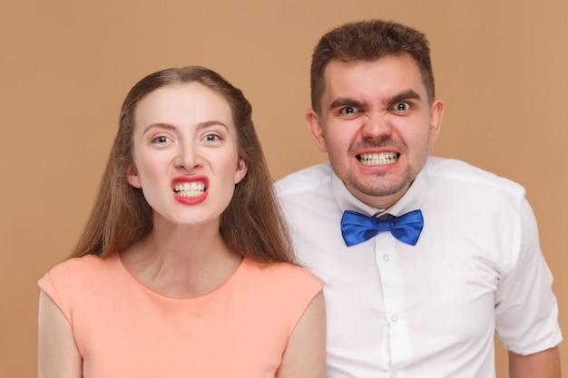Молодая пара смотрит в камеру с забавным лицом и показывает свои стиснутые зубы