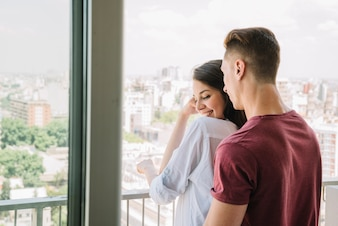 Young couple looking atcity from balcony
