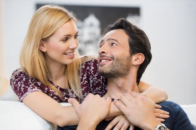 お互いを見て、リビングルームで抱き合っている若いカップル。