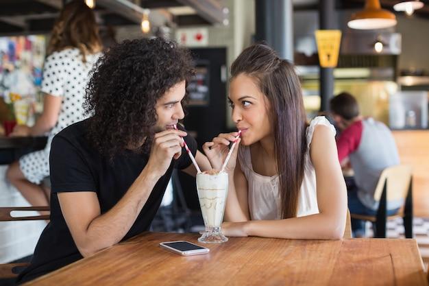 レストランで一緒にドリンクを飲みながらお互いを見て若いカップル