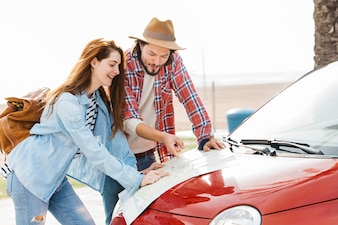 Young couple looking at road map on red car