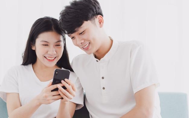 Молодая пара, глядя на телефон вместе с счастливым выражением лица