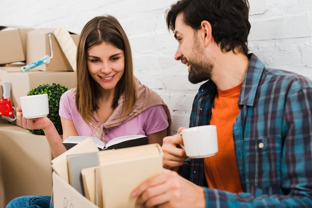 Young couple looking at books in the cardboard box holding coffee cups in hand