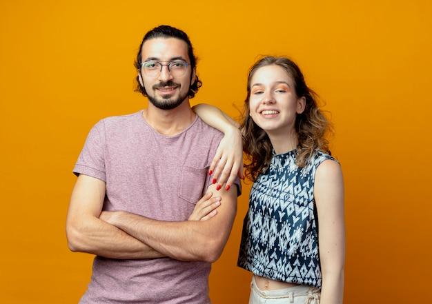 Coppia giovane guardando la telecamera sorridendo felice e positivo in piedi su sfondo arancione