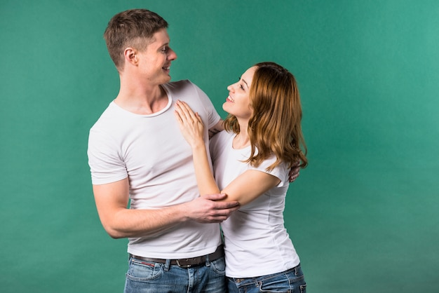 Young couple looking to each other against green background