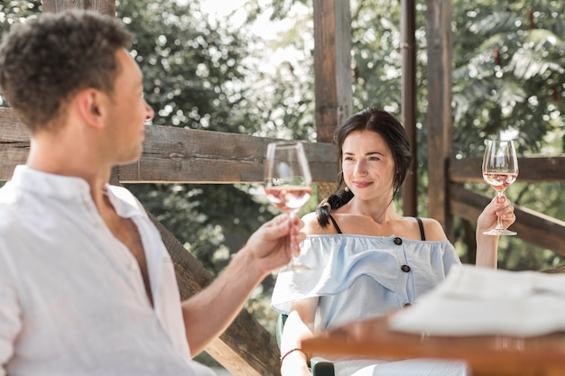 Young couple looking at each other raising wine toast