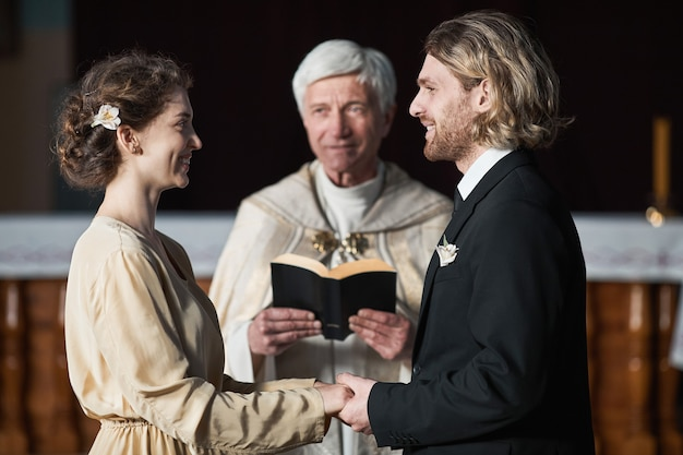 Young couple looking at each other and smiling during wedding ceremony with priest in the church