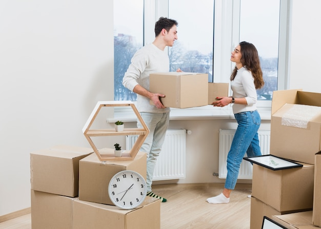 Young couple looking at each other unpacking the moving cardboard boxes at home