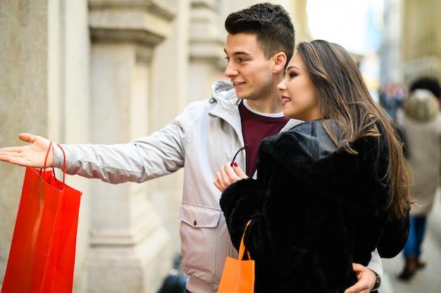 Молодая пара ищет возбужденных на витрине магазина шил