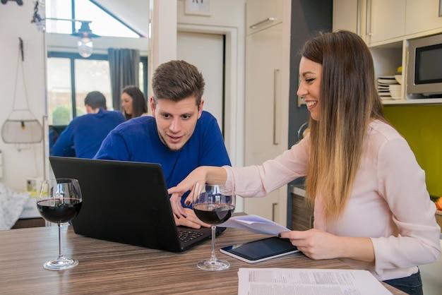 Молодая пара ищет финансовые документы в ноутбуке за столом в домашнем интерьере. молодые домашние студенты, представляющие услуги электронного обучения