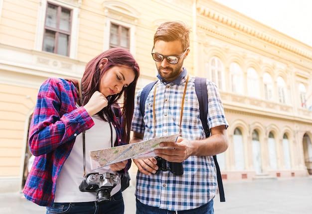 地図で方向を探している若いカップル