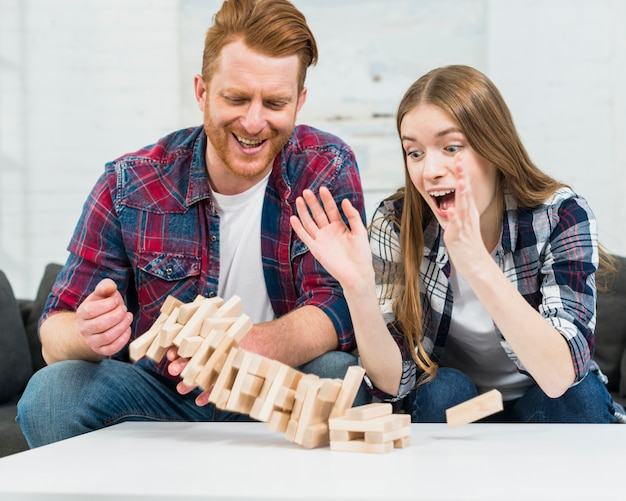 Young couple looking at jenga tower collapses on white table surface