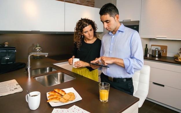 仕事に行く前に家で速いコーヒーを飲みながら電子タブレットでニュースを探している若いカップル