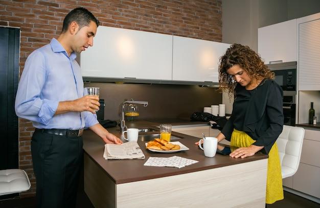 仕事に行く前に家で速い朝食をしながら新聞や電子タブレットでニュースを探している若いカップル