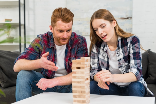 Young couple looking out the wooden block stack tower game on table