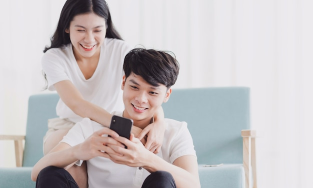 Young couple looking at the phone together with happy expression