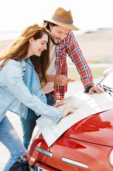 Young couple looking at road map on car