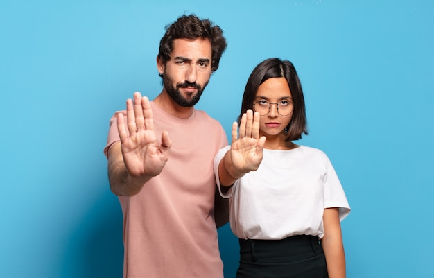 Young couple looking serious, stern, displeased and angry showing open palm making stop gesture