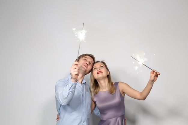 Молодая пара смотрит на бенгальские огни на белой стене