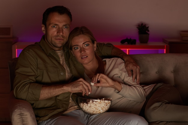 매우 두려워 보이는 젊은 부부는 팝콘과 함께 소파에 누워 무서운 영화를보고