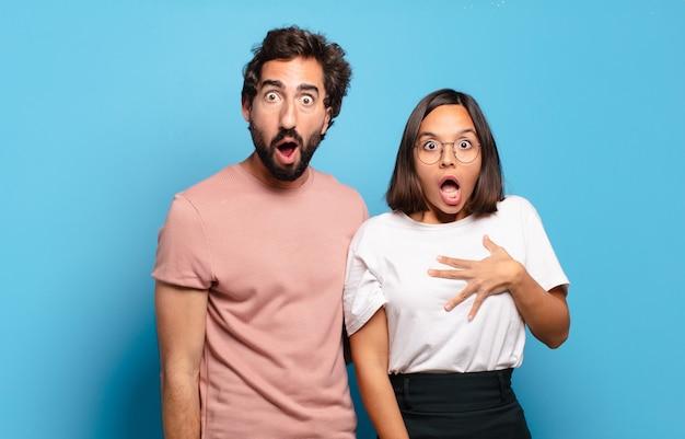 非常にショックを受けた、または驚いたように見える若いカップルは、すごいことを言って口を開けて見つめています