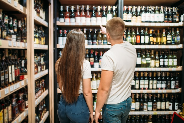 Young couple looking for wine in alcohol market