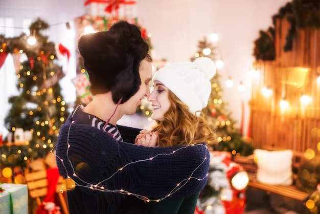 A young couple in love against christmas trees with garlands. a young man in a hat with earflaps warms the hands of a beautiful girl, wrapped in a scarf.