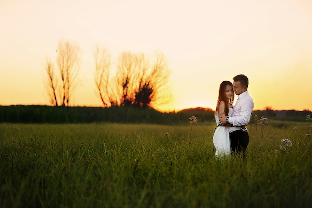 Young couple in love are hugging outdoors in the field at sunset on summer day.