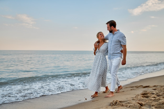 A young couple in love are walking along the seashore, enjoying each other and their vacation, romantically spending time on the beach.