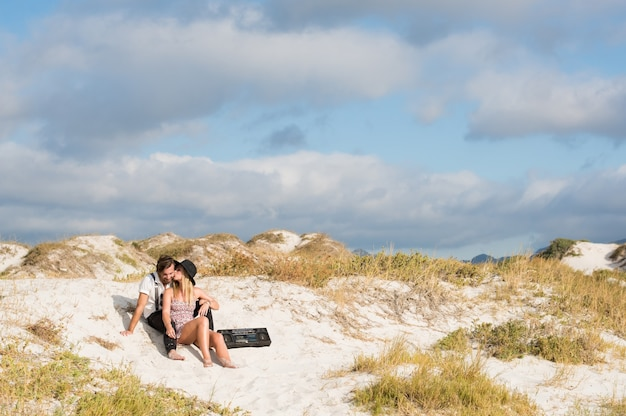 Young couple in love at the beach sitting and listening music with vintage radio
