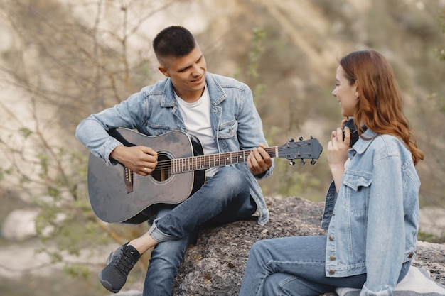 Young couple in love, boyfriend playing the guitar