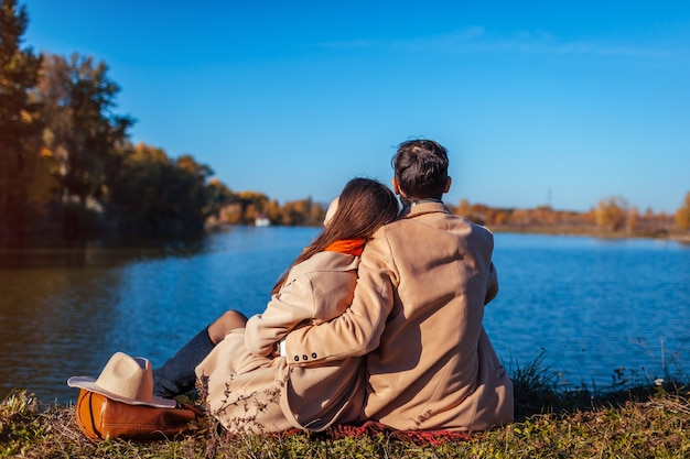 Young couple in love chilling by autumn lake. happy man and woman enjoying nature and hugging. relaxing outdoors