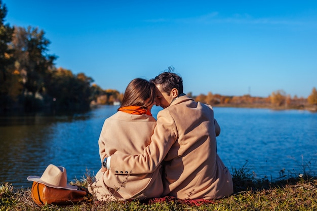 Young couple in love chilling by autumn lake happy man and woman hugging